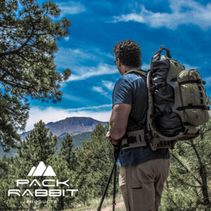 Hiker wearing green backpack looking out at mountains