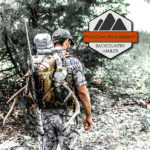 Hunter wearing tan backpack carrying elk horns and rifle