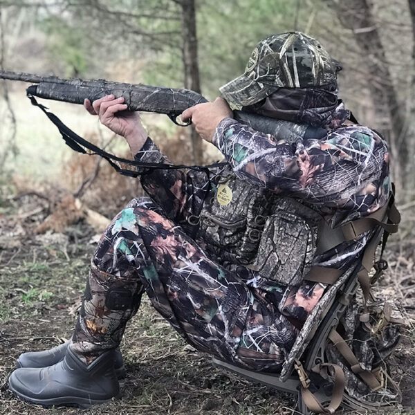 Turkey hunter wearing camouflage chest pack and sitting in backpack seat shooting in woods