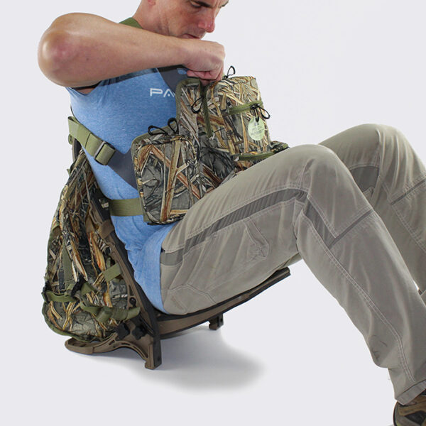 Man wearing camouflage chest pack and sitting in backpack seat with white background