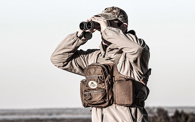 Man wearing tan chest pack looking through binoculars