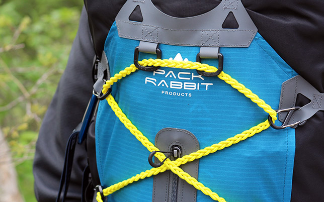Close up of yellow bungie cord on blue backpack