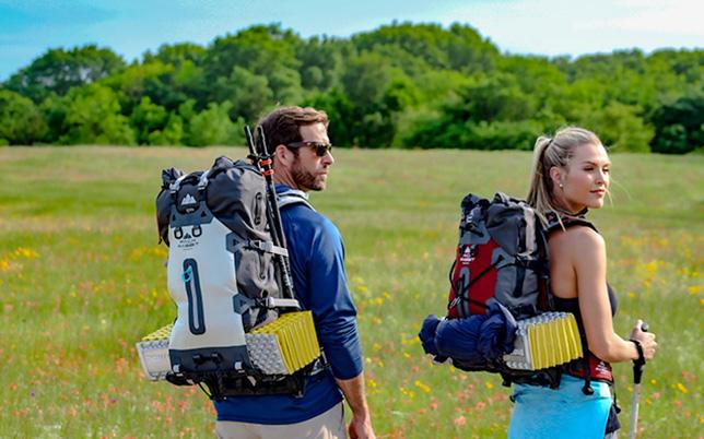 Couple wearing backpacks hiking through spring flowers