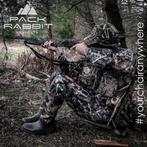 Turkey hunter wearing camouflage chest pack and sitting in backpack seat shooting shotgun