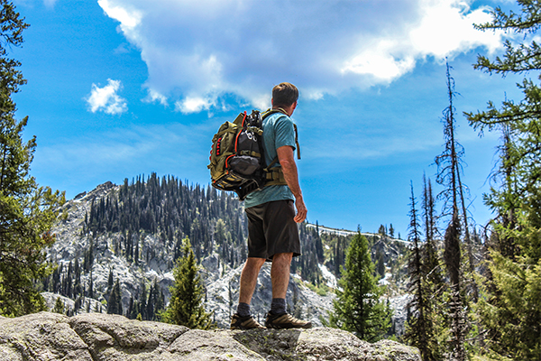 Hiker wearing green backpack looking at mountain