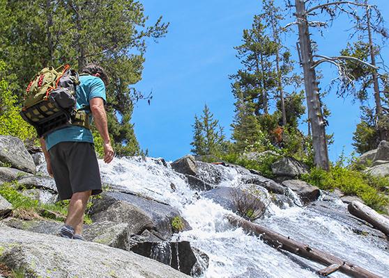 Hiker wearing a green backpack crossing a waterfall