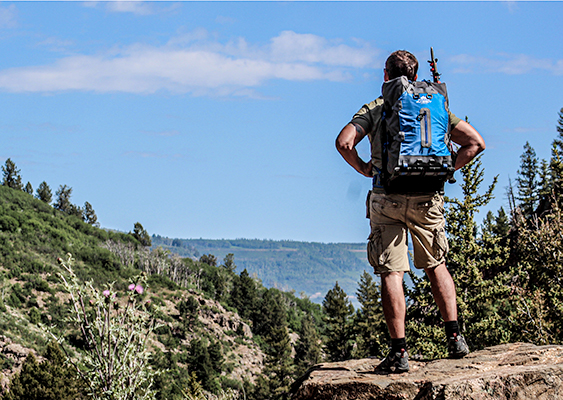 Hiker wearing blue backpack overlooking a valley
