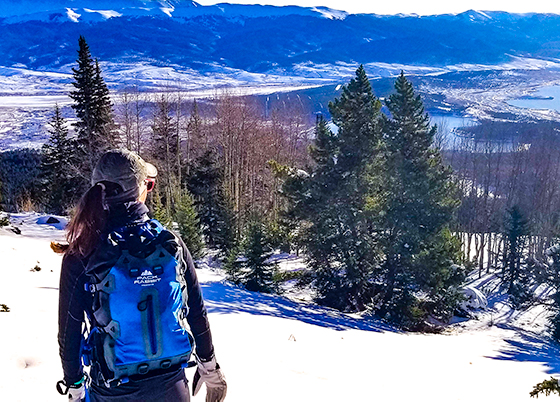 woman hiker wearing a blue backpack looking over a snow covered valley