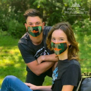 young couple wearing face masks in woods