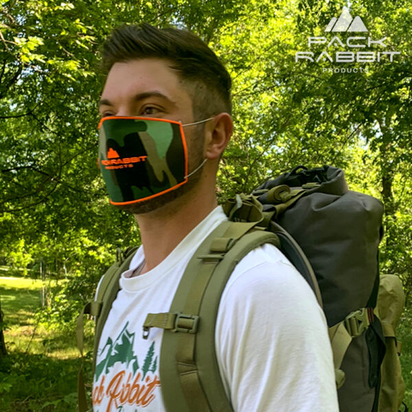 man wearing camo face mask and backpack in woods